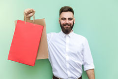 Young adult bearded man holding with many shopping bags at mall or store. Royalty Free Stock Images