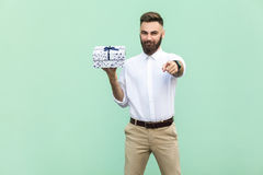 Young adult bearded man, pointing at camera and holding a gift box. Stock Photo