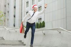 Young adult bearded man in santa hat holding many shopping bags and gifts and running to kids. Stock Photo