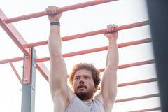 Young adult bearded redhead man, climb on bar Stock Photo