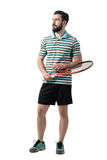 Young adult bearded tennis player holding ball and racket looking away. Full body length portrait isolated over white studio background Stock Photo
