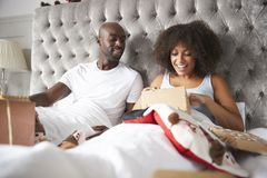 Young adult black couple opening gifts in bed on Christmas morning, low angle stock photo