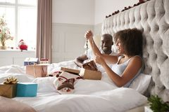 Young adult black woman sitting up in bed on Christmas morning with her partner admiring her present, side view. Young adult black women sitting up in bed on royalty free stock photo