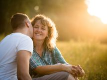 Young adult boy kissing her mother on cheek. Son kissing her affectionate mother, sunset background Royalty Free Stock Photography