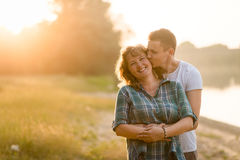 Young adult boy kissing his mother with love Stock Photos