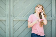 Young Adult Brown Eyed Teen Girl Listens To Music on Her Smart Phone. Outdoor Portrait of Young Adult Brown Eyed Woman Listening To Music with Earphones on Her Stock Images