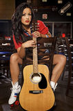 Young adult brunette woman with guitar Royalty Free Stock Photo
