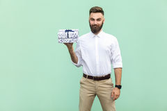Young adult businessman holding gift box and looking at camera and toothy smile. On light green background. Studio shot Royalty Free Stock Photography