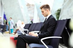 Young adult using laptop in airport lounge. Young adult businessman using laptop in airport lounge Royalty Free Stock Photo