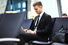 Young adult using laptop in airport lounge. Young adult businessman using laptop in airport lounge Stock Images