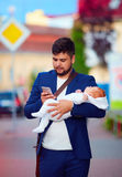 Young adult businessman walking through the city with newborn baby on hands Stock Image