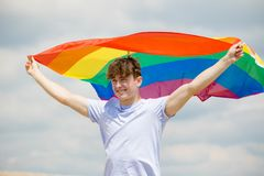 Caucasian male on a beach holding a Pride flag. Young adult caucasian male holding on a beach holding the Pride flag stock photos