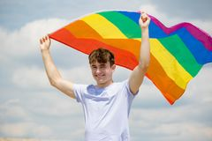 Caucasian male on a beach holding a Pride flag. Young adult caucasian male holding on a beach holding the Pride flag royalty free stock image