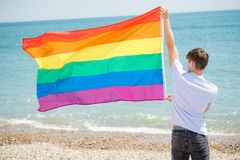 Caucasian male on a beach holding a Pride flag. Young adult caucasian male holding on a beach holding the Pride flag royalty free stock images