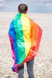 Caucasian male on a beach holding a Pride flag. Young adult caucasian male holding on a beach holding the Pride flag royalty free stock photo