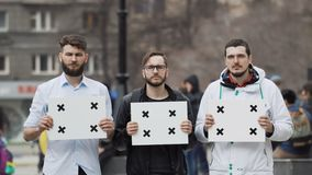 Young adult Caucasian people look into the camera at demonstration. Serious guys. 3 people at the demonstration with banners in their hands look into camera and