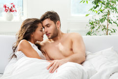 Young adult couple in bedroom. Young adult heterosexual couple lying on bed in bedroom stock images