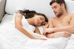 Young adult couple in bedroom. Young adult heterosexual couple lying on bed in bedroom royalty free stock photo