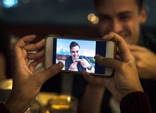 Young adult couple on a dinner date taking photos using smartphone Stock Photos