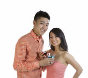 Young Adult Couple Expressing Happiness Together while sharing a Royalty Free Stock Photography