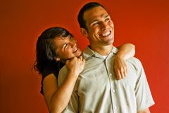 Young Adult Couple Hugging Smiling. Young adult couple hugging, smiling, and in love, against a red background Stock Image