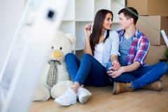 Young Adult Couple Inside Room with Boxes Holding New House Keys. Banner stock images