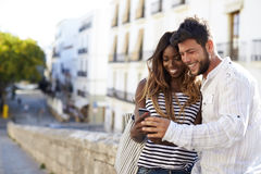 Young adult couple looking at smartphone, Ibiza, Spain Royalty Free Stock Images