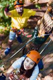 Couple in love enjoy active leisure in extreme rope park. Young adult couple in love, climbers with protective sport equipment and helmets climb and enjoy active royalty free stock photography