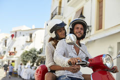 Young adult couple on a motor scooter in a street, Ibiza Stock Photo