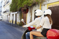Young adult couple on a motor scooter in a street, Ibiza Royalty Free Stock Image