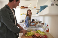 Young adult couple  preparing food look at each other Stock Photo