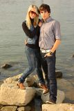 Young adult couple by a river. S tanding on rocks Stock Images