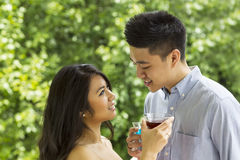 Young Adult Couple sharing a drink with each other outdoors Royalty Free Stock Photography