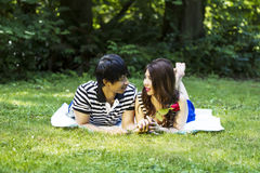 Young Adult Couple Sharing Their Love While Lying on a Blanket O Royalty Free Stock Photography