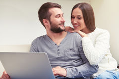 Young adult couple sitting on sofa Stock Photos