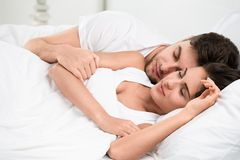 Young adult couple sleeping in bedroom. Young adult couple sleeping on the bed in bedroom royalty free stock images