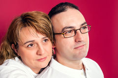Young Adult Couple Smiling. Over a Red Background stock photography