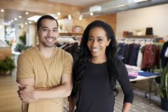 Young adult couple smiling to camera in a clothes shop royalty free stock photo