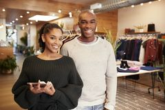 Young adult couple smiling to camera in a clothes shop stock image