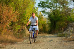 Young adult cyclist riding mountain bike in the countryside Stock Images