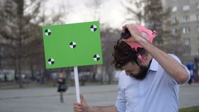 A boy in a pink gas mask at a rally with a banner in his hands closeup 4k. A young adult at a demonstration or strike looking into camera. A serious guy takes