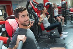 Young adult doing powerlifting on machines in fitness club stock images