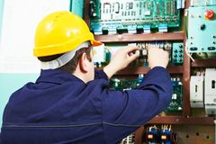 Adult electrician builder engineer worker testing electronics in switch board stock photography