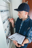 Young adult electrician in front fuse switch board Royalty Free Stock Image