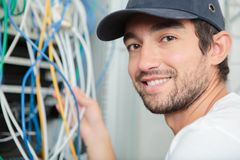Young adult electrician in front fuse switch board. Young adult electrician in front of fuse switch board Royalty Free Stock Photography