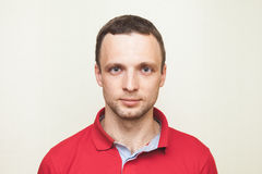 Young adult European man in red polo shirt Stock Images