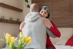 Young adult female cancer patient hugging her husband at home after treatment in hospital. Cancer and family support. stock photography
