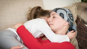 Young adult female cancer patient spending time with her daughter at home, relaxing on the couch. Cancer and family support concept stock images