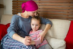 Young adult female cancer patient spending time with her daughter at home, relaxing on couch. Cancer and family support concept. Young adult female cancer royalty free stock photos
