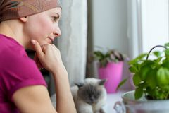 Young adult female cancer patient wearing headscarf and bathrobe sitting in the kitchen with her pet cat. Young adult female cancer patient wearing headscarf Royalty Free Stock Photography